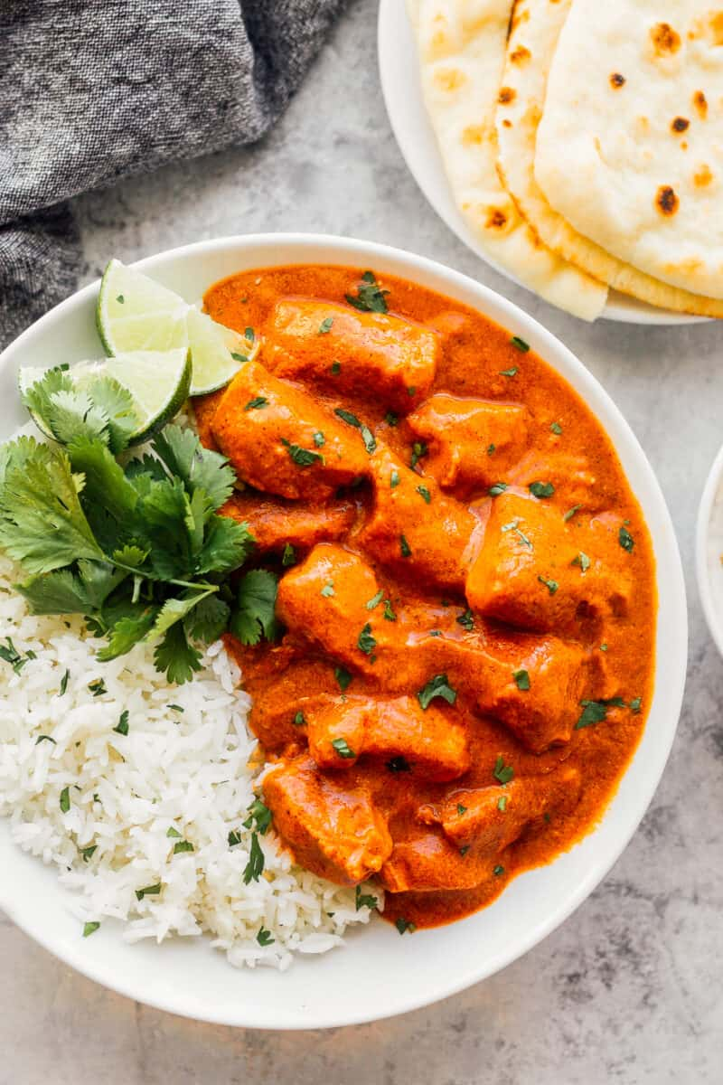 butter chicken with rice and cilantro in white bowl