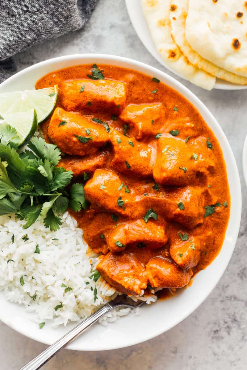 butter chicken with white rice garnished with cilantro