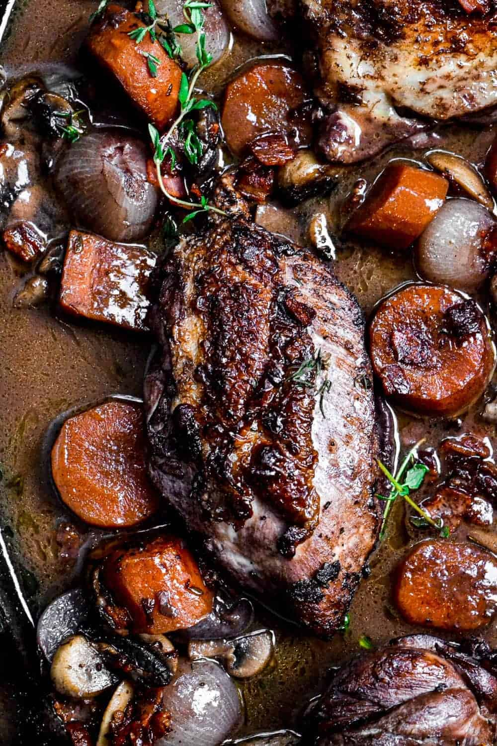 Close up of a cooked chicken breast in red wine sauce