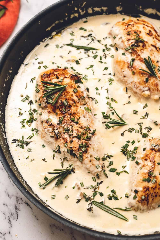 chicken in skillet with garlic herb sauce