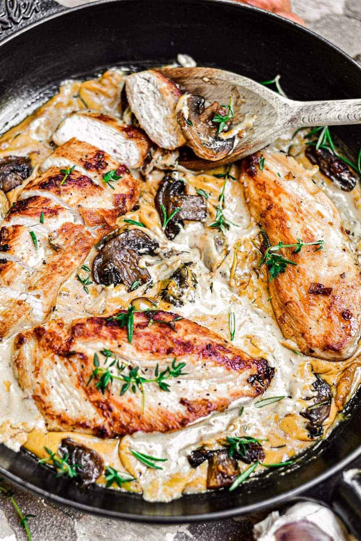 Stirring the Creamy Garlic Herb Chicken Skillet with a wooden spoon