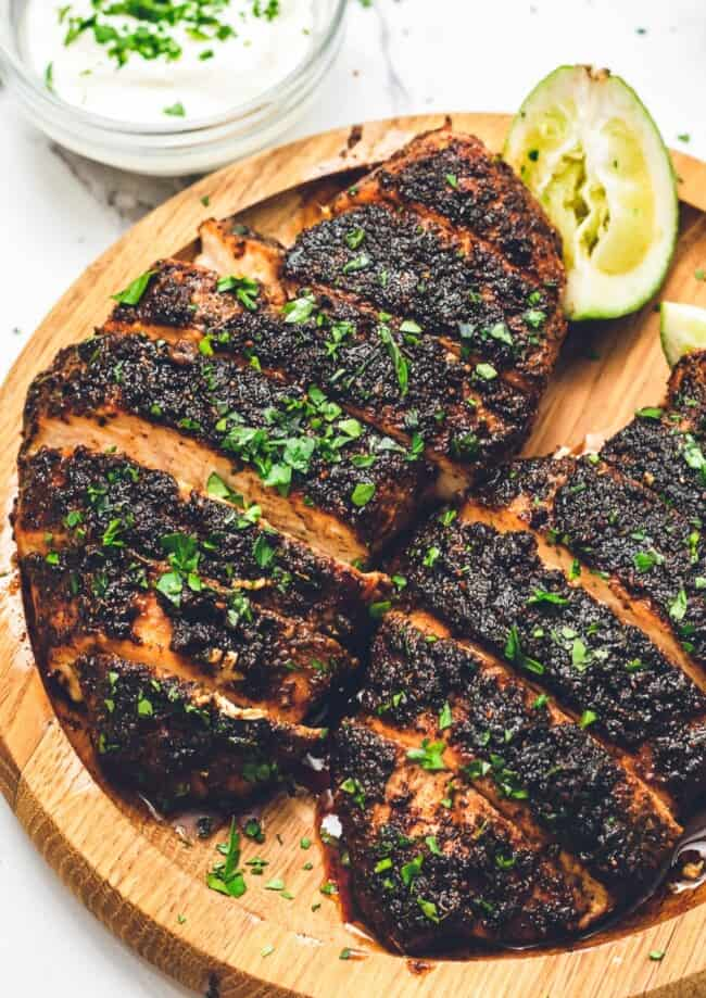 up close image of blackened chicken on wooden plate