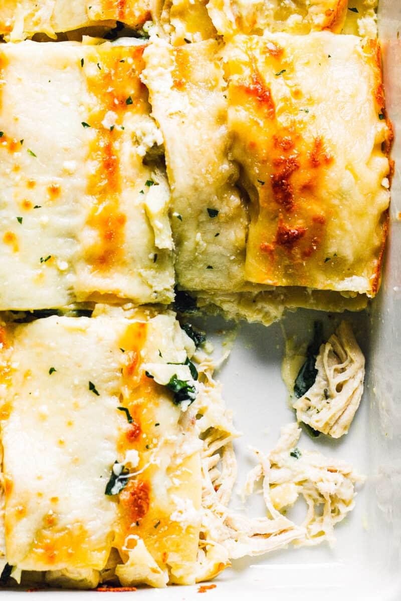 up close sliced white chicken lasagna in baking dish