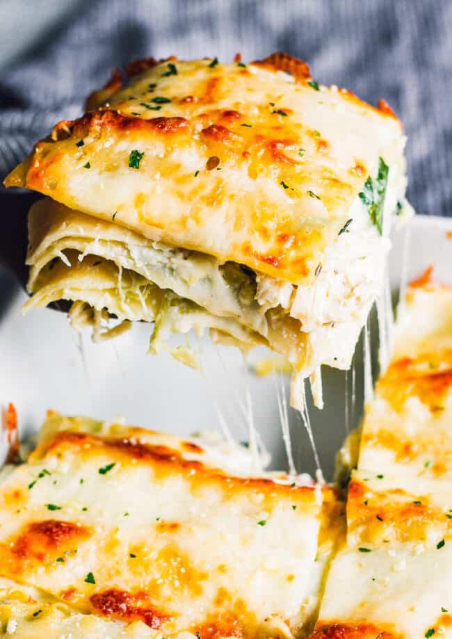 lifting up slice of white chicken lasagna