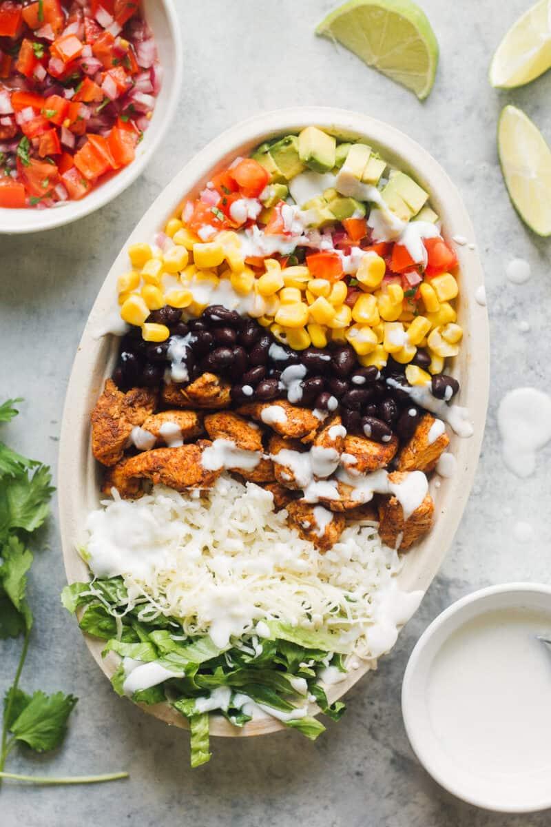 layered chicken burrito bowl next to ingredients