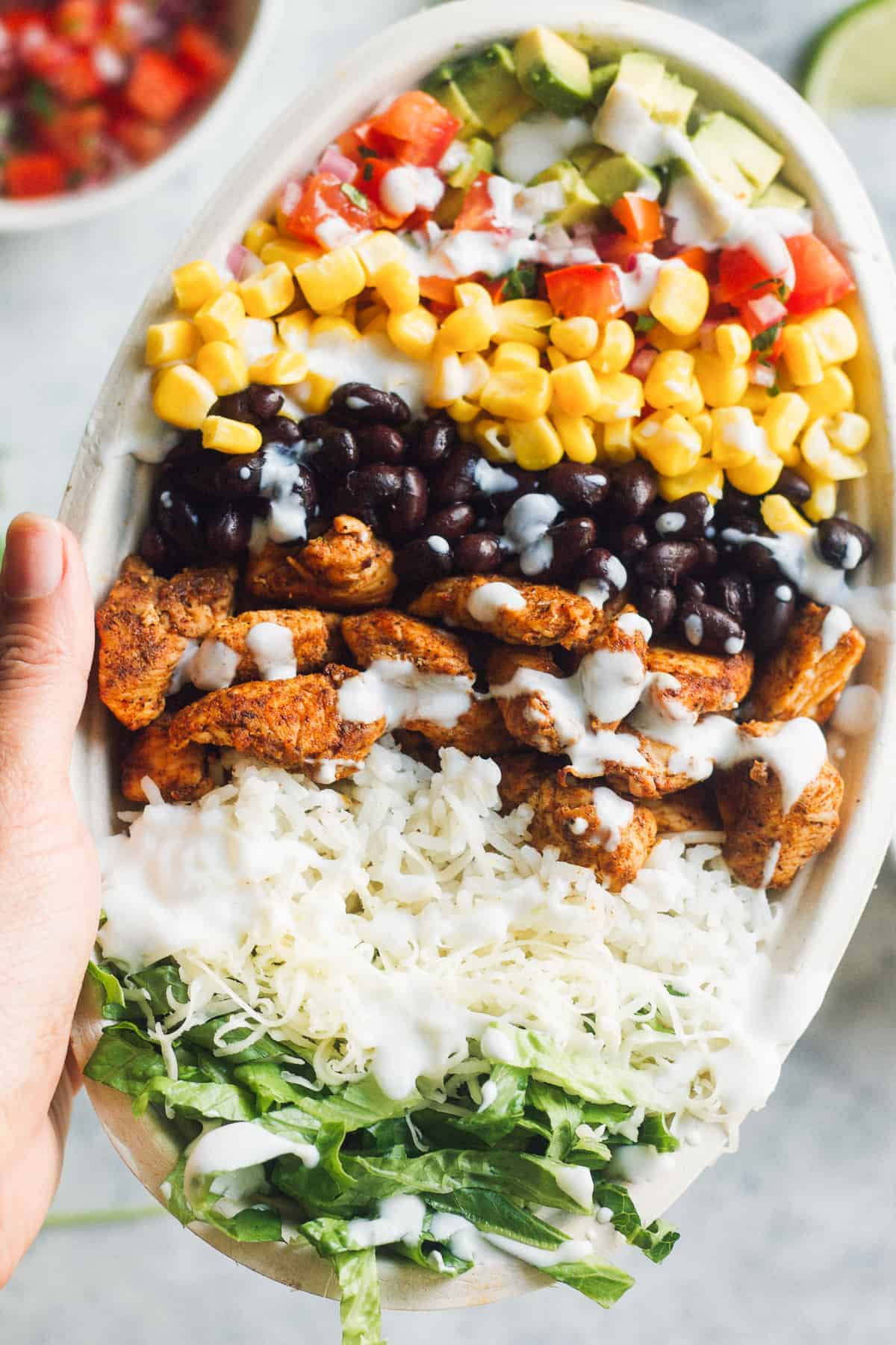 hand holding up copycat chipotle chicken burrito bowl