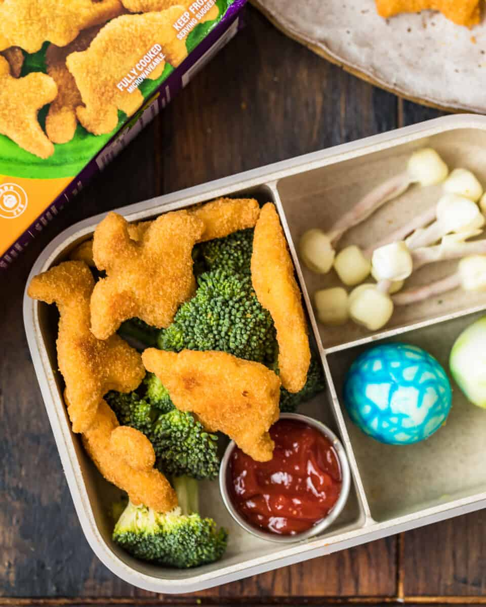 overhead shot of bento box made with dinosaur chicken nuggets and other dino food ideas
