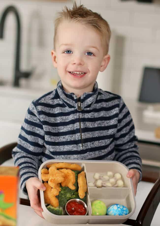 henry holding dinosaur themed lunchbox