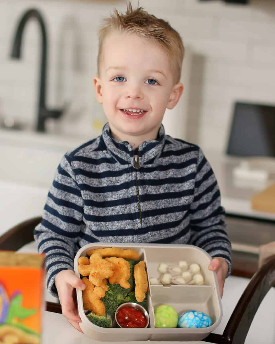 little boy holding up dinosaur themed lunch box