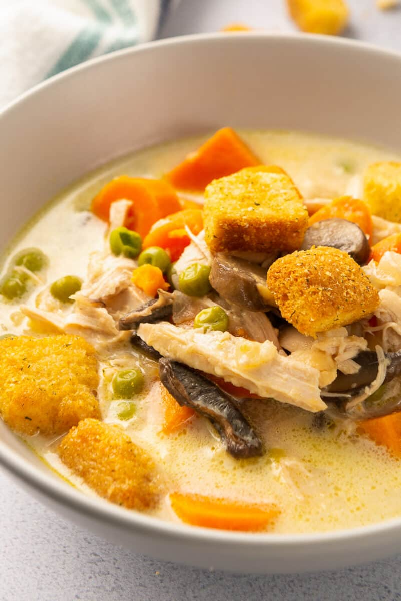 up close image of chicken soup with carrots, croutons, peas, and mushrooms
