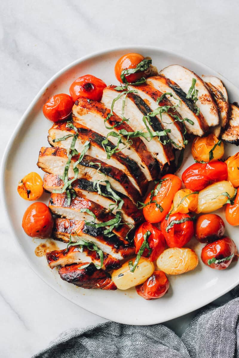 sliced balsamic chicken on plate with tomatoes