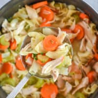 scoop of chicken noodle soup over pot