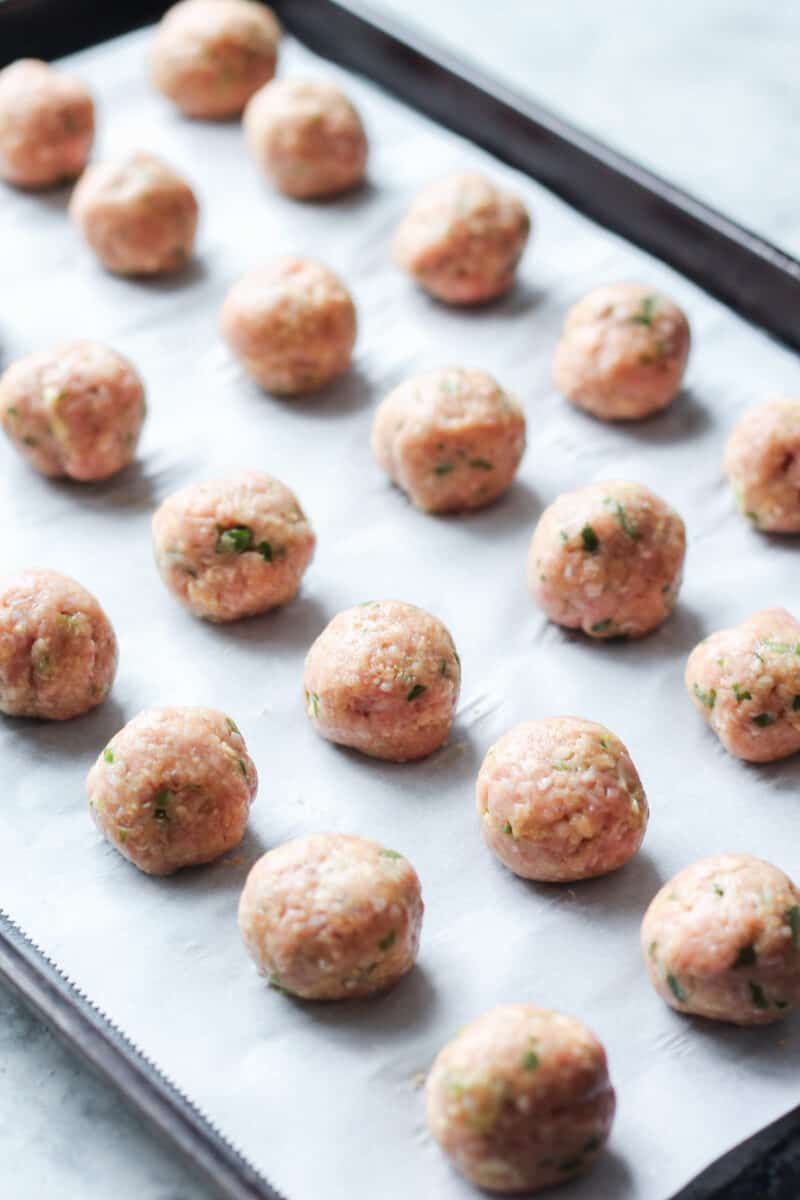 Unbaked chicken meatballs on a baking sheet