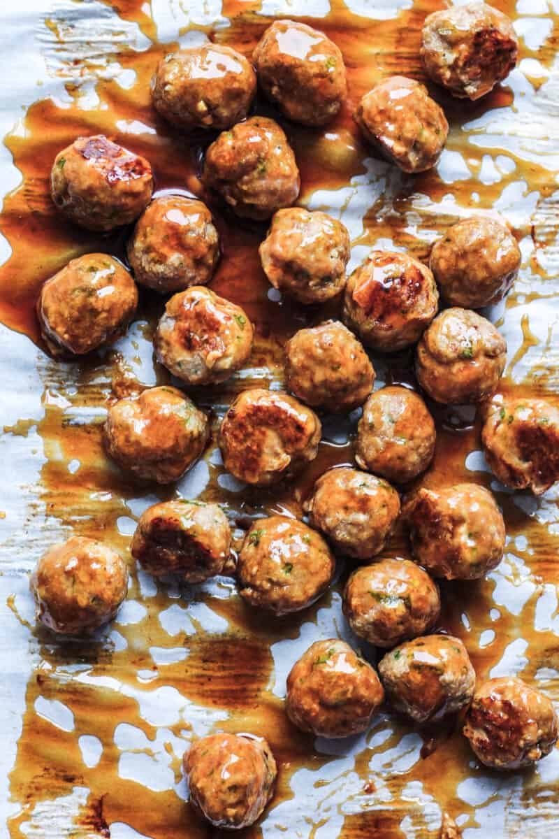 Chicken meatballs on parchment covered in the Asian sauce