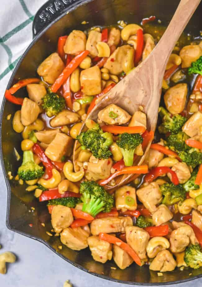 chicken teriyaki stir fry in skillet with wooden spoon