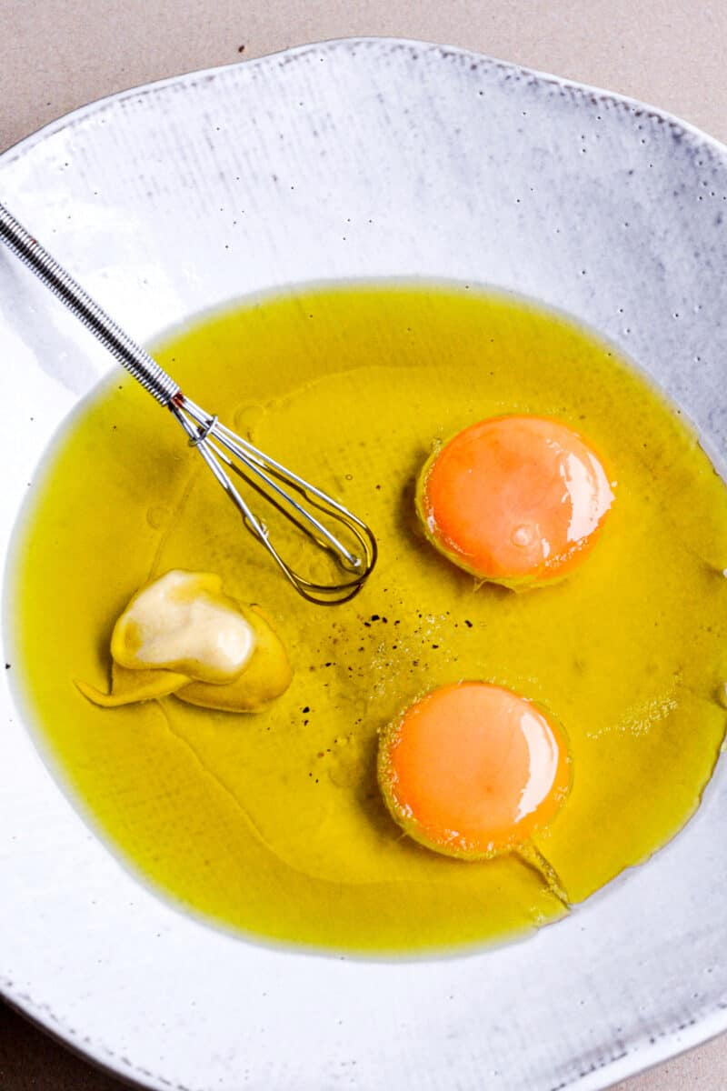 Ingredients for Homemade Mayonnaise in a bowl with a whisk