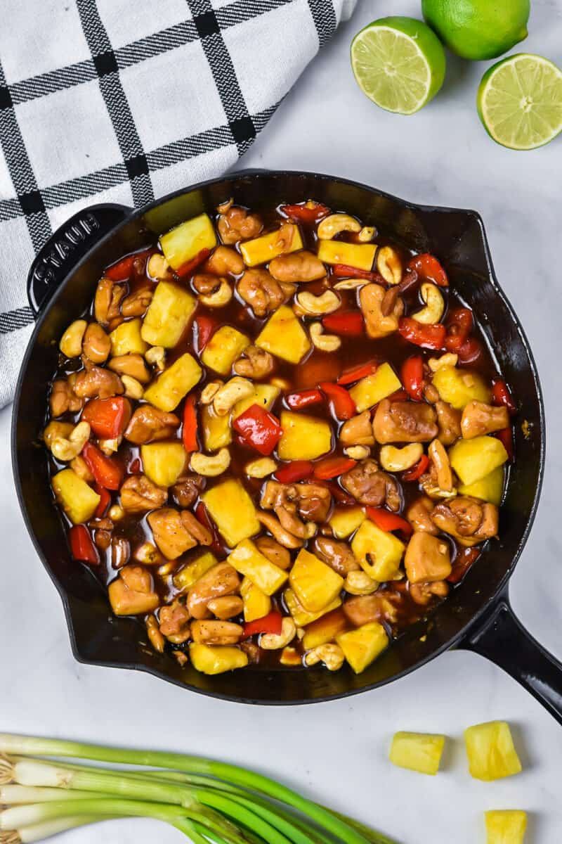 Pineapple chicken in a skillet next to some of the ingredients used