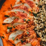 romesco chicken on a plate with sauce and rice