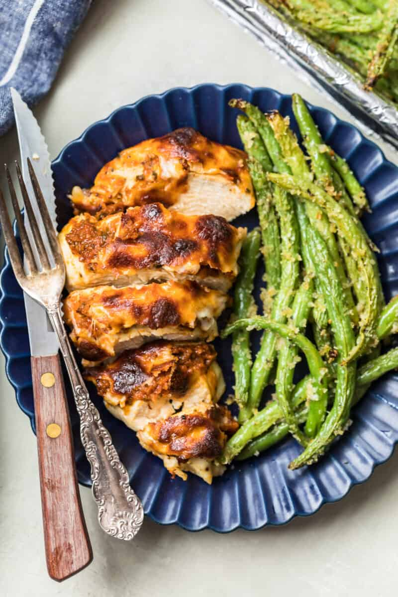 Pesto Mozzarella Chicken and green beans served on a plate with a knife and fork