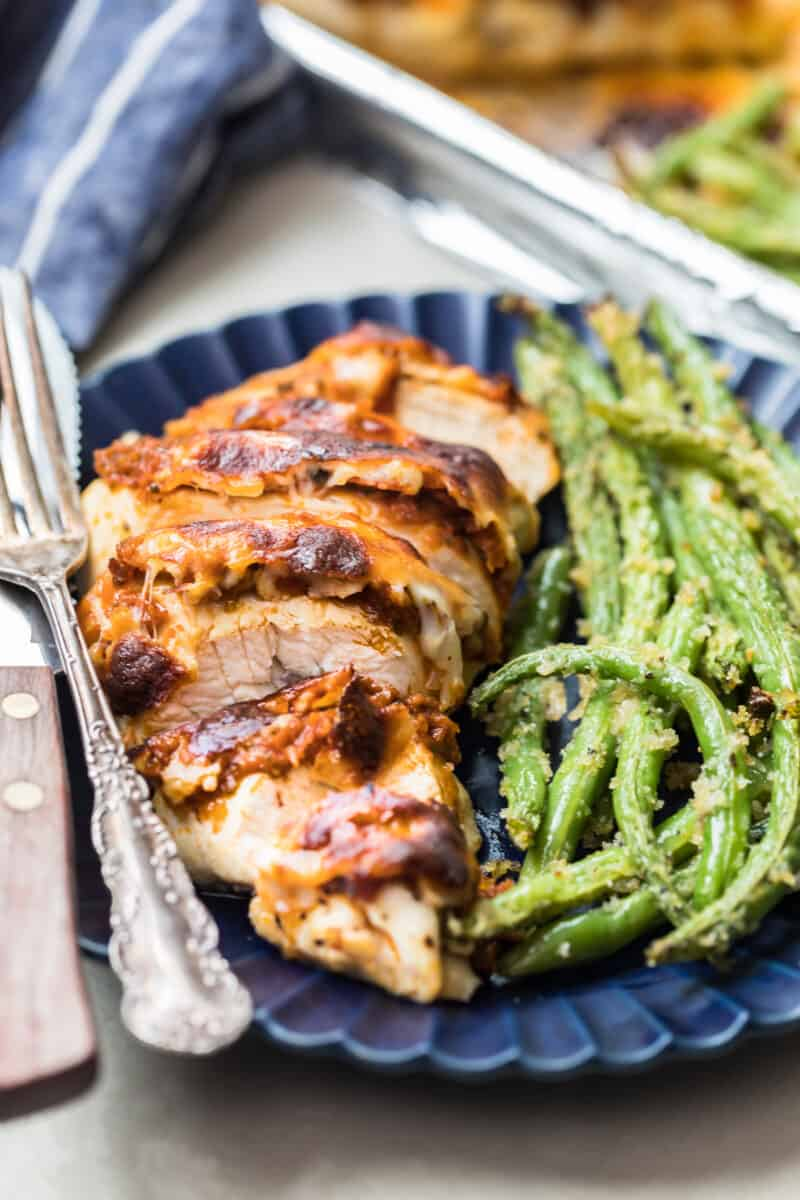 Pesto Mozzarella Chicken cut into slices and served with the green beans