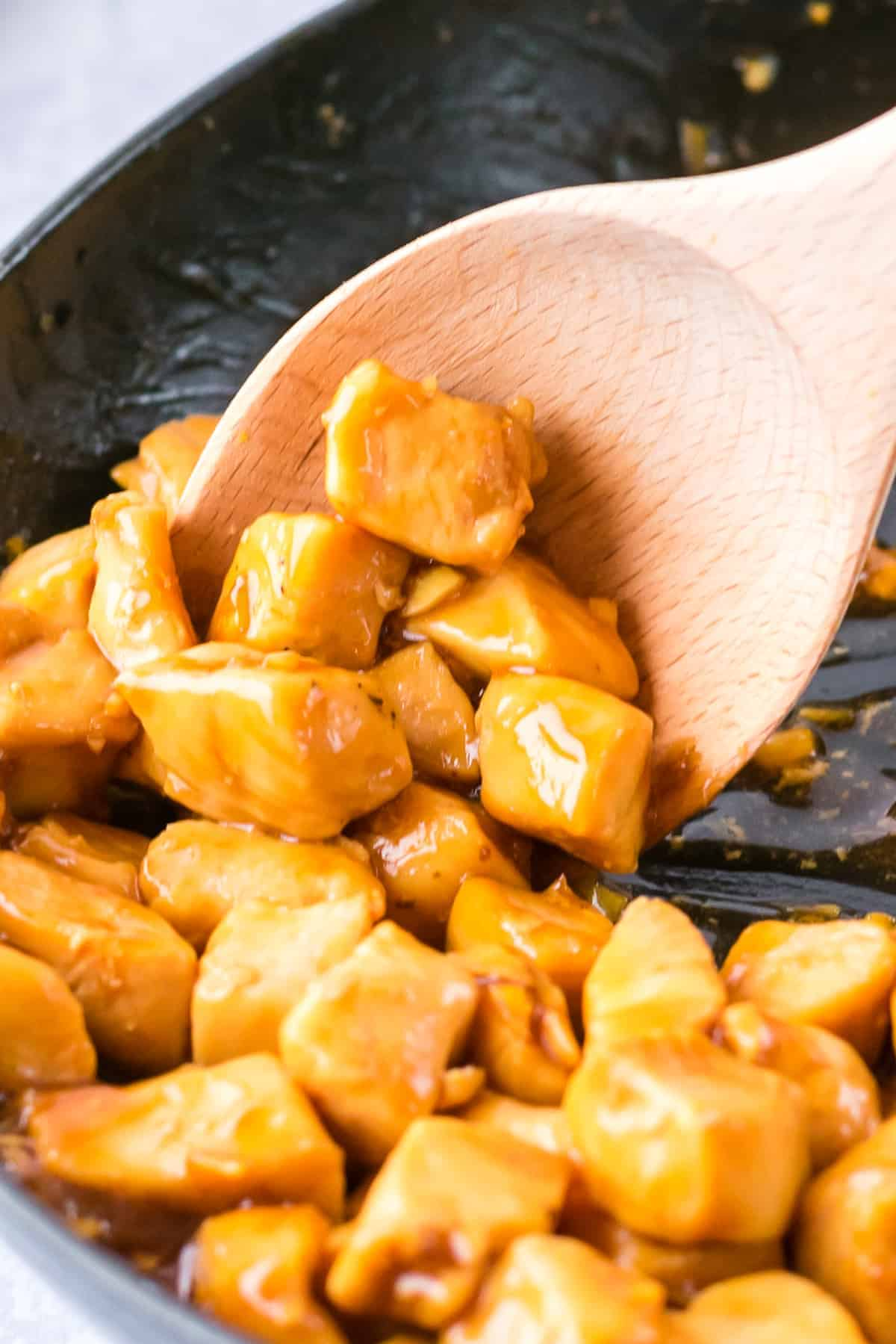 spoon lifting up diced teriyaki chicken breast
