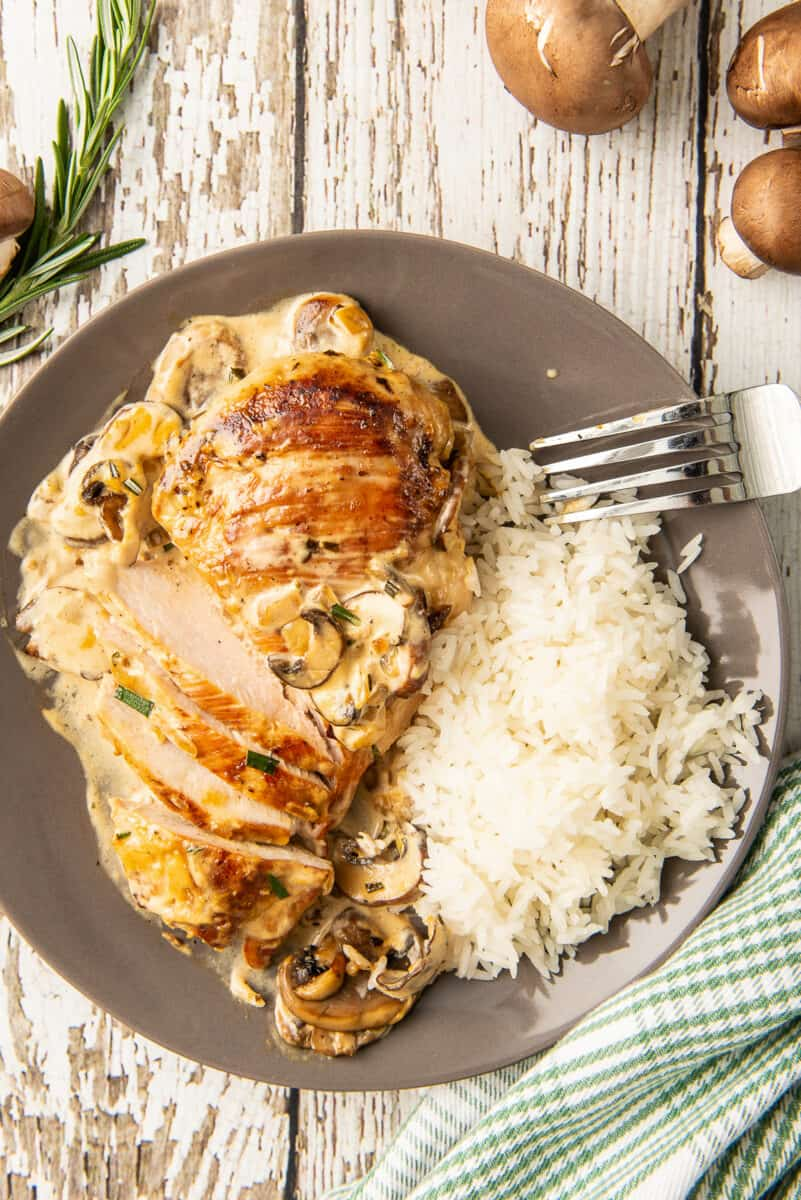 overhead image of sliced chicken in mushroom cream sauce on plate with rice