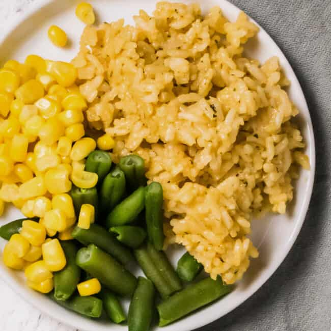 plate with chicken rice, green beans, and corn