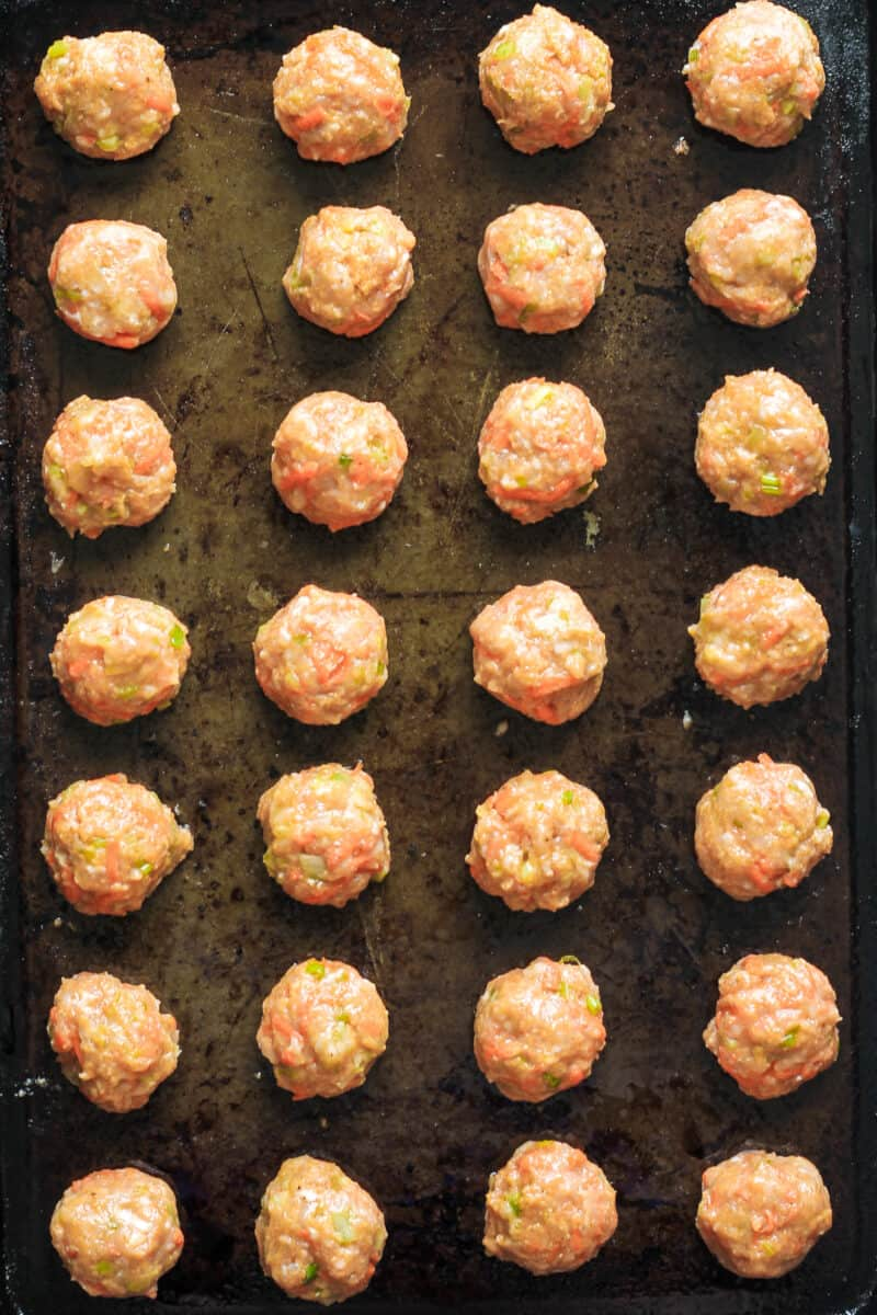 uncooked chicken meatballs on sheet pan