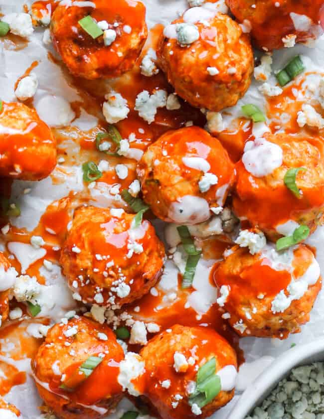 up close image of buffalo chicken meatballs drizzled with ranch