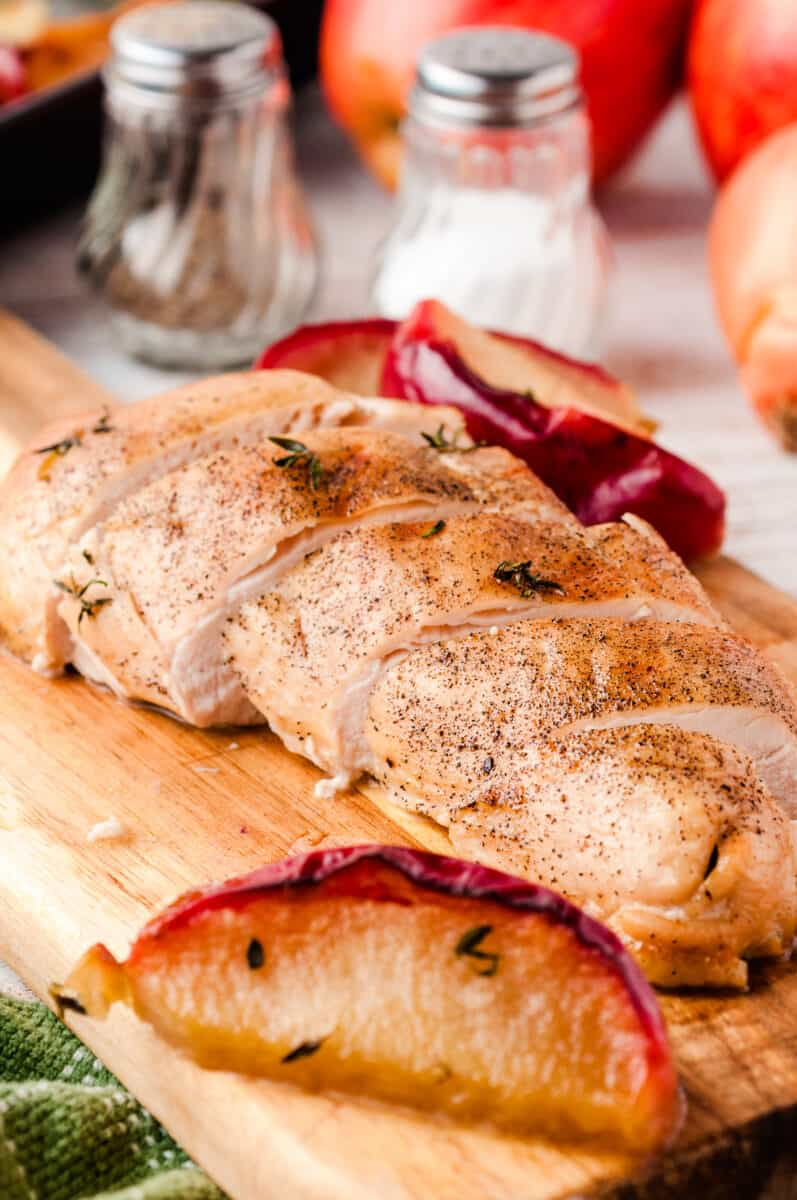 cutting board with sliced chicken breast, apple slices, and onion
