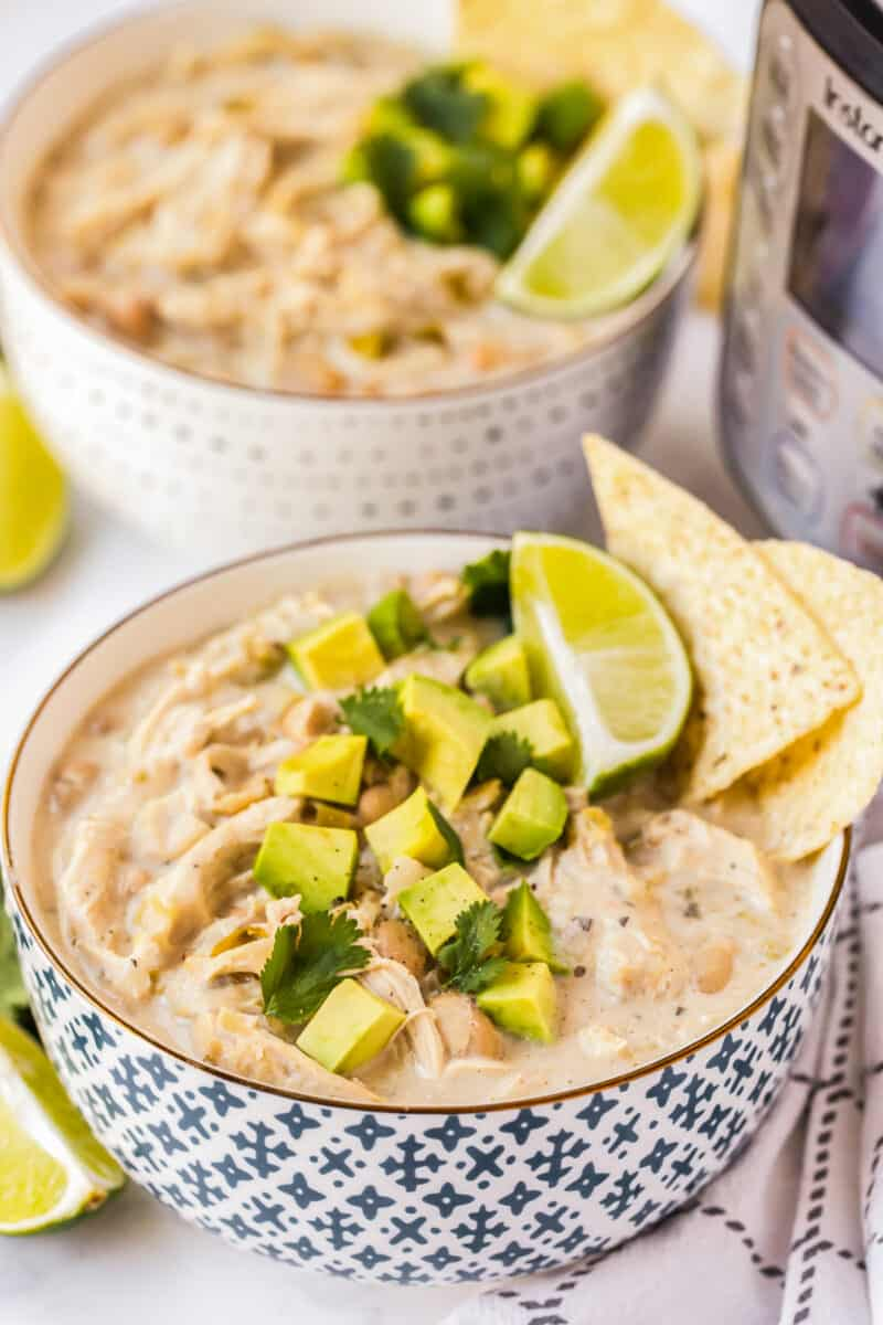 bowl of white chicken chili garnished with avocado and chips