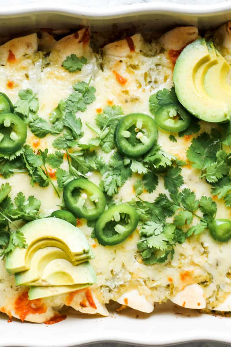 up close image of green chile salsa verde chicken enchiladas in pan