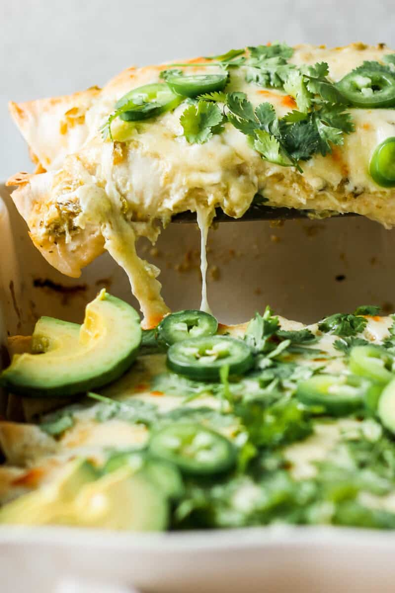 lifting up chicken enchiladas with cheese garnished in pan