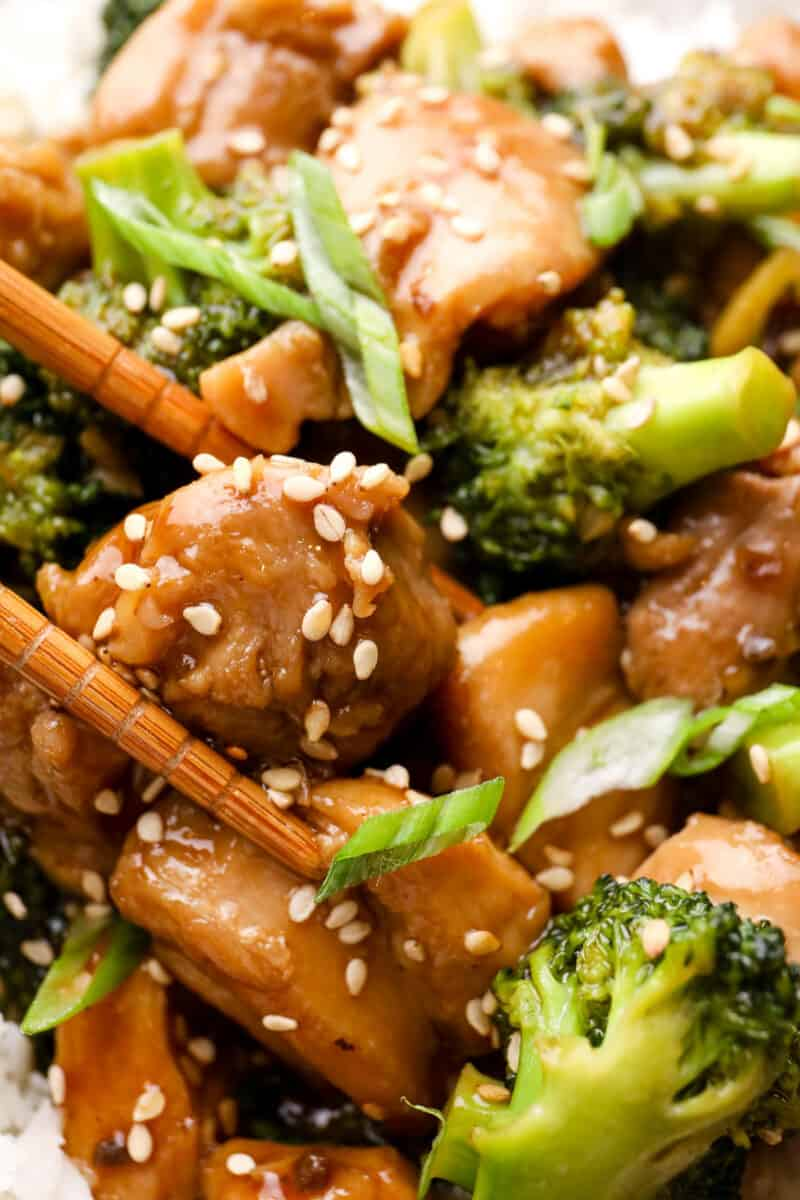 up close image of teriyaki chicken thighs garnished with sesame seeds being picked up by chopsticks