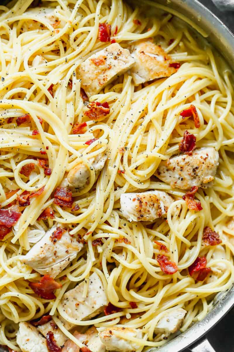 up close image of pasta with cream sauce, bacon, and chicken