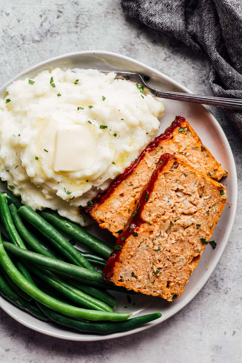chicken meatloaf on plate with green beans and mashed potatoes