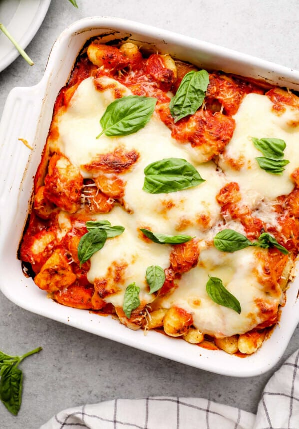 white pan with chicken parm gnocchi bake topped with fresh basil