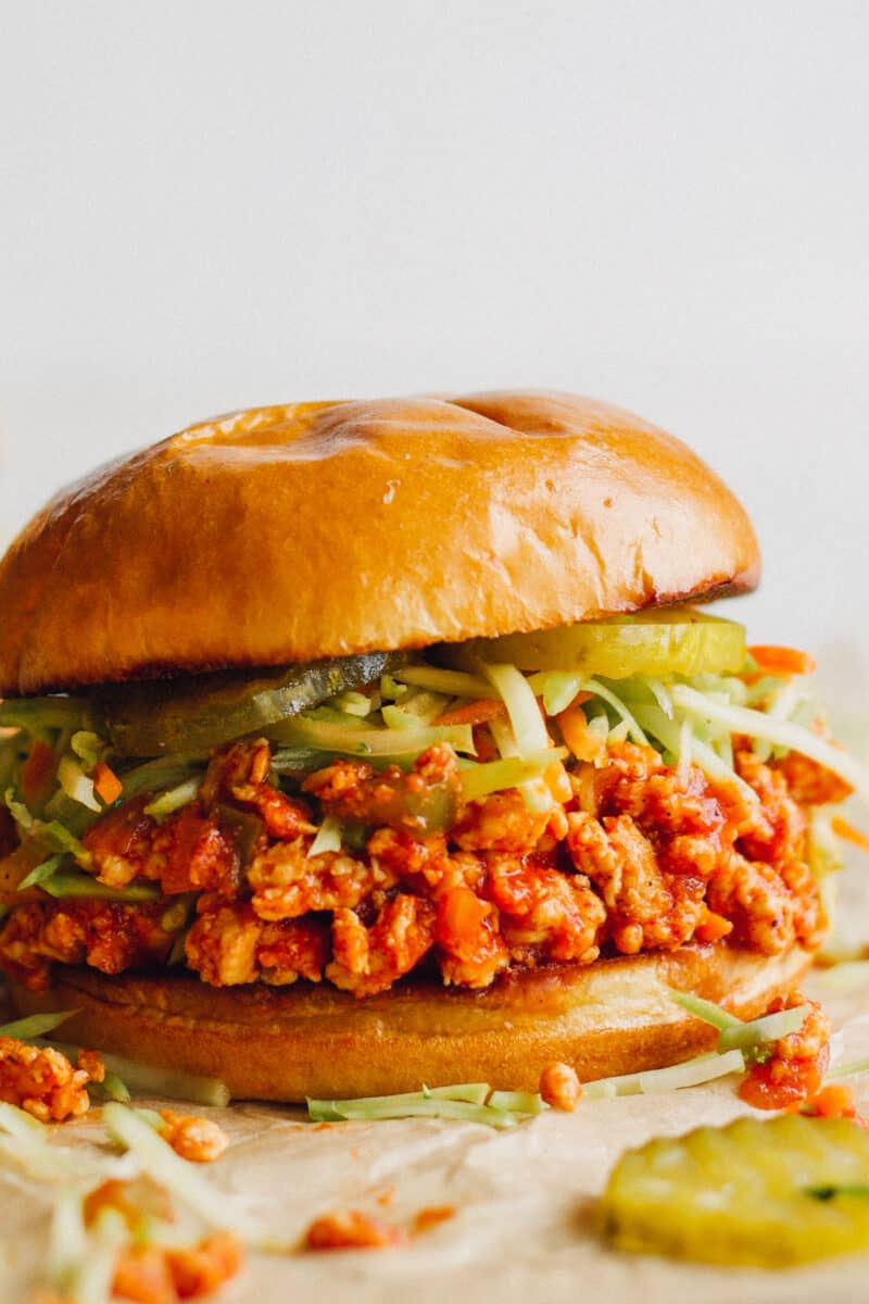 up close image of chicken sloppy joes topped with slaw and pickles