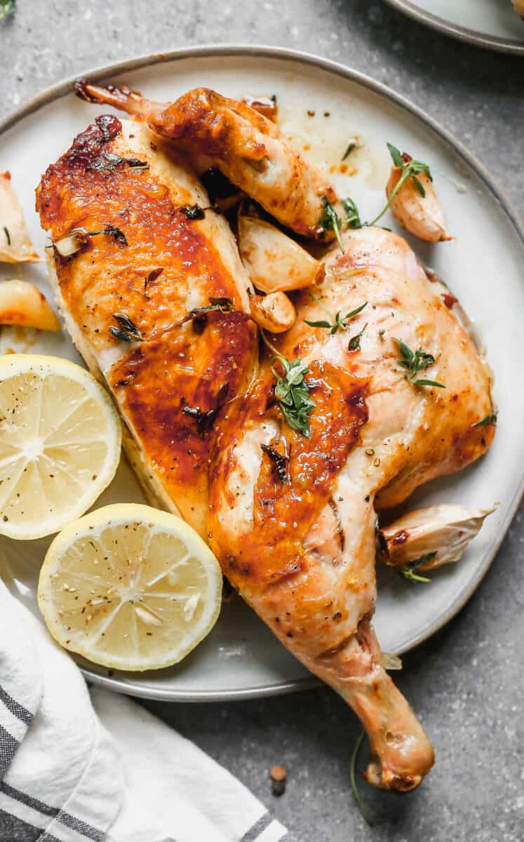 chicken under a brick on plate with lemon and parsley