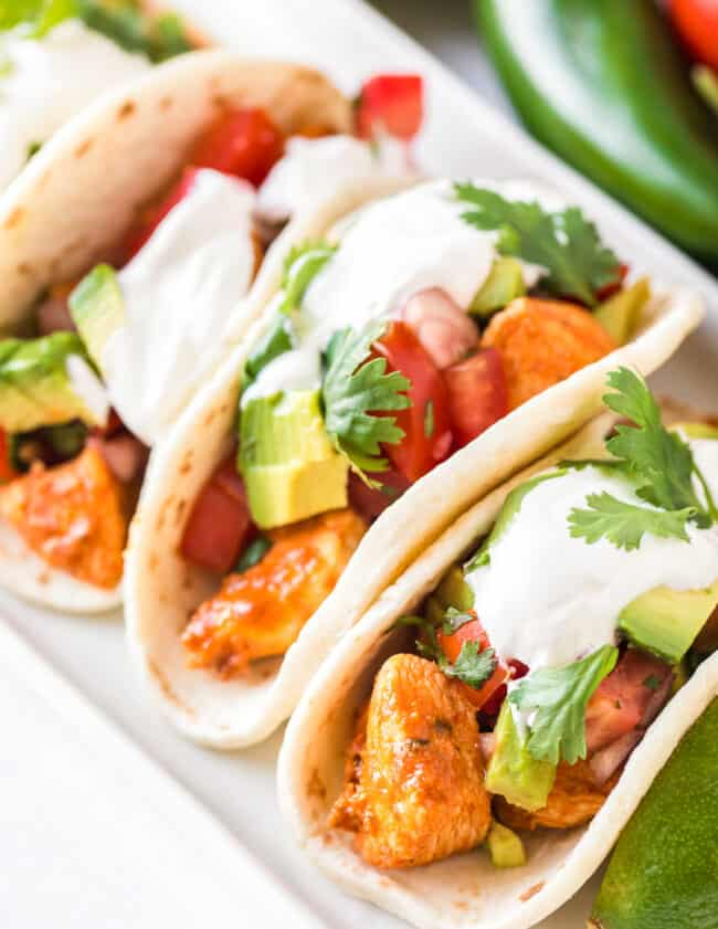 easy chicken tacos topped with avocado and sour cream