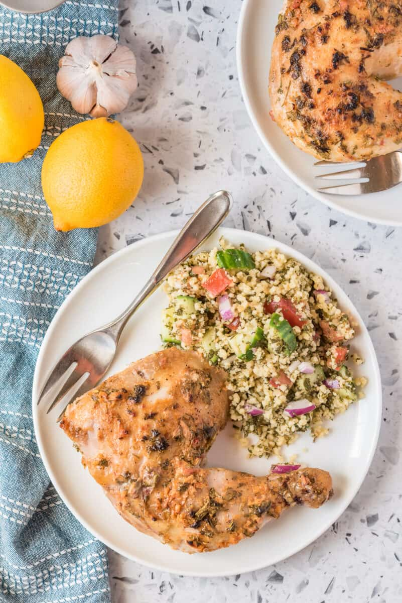 chicken leg on plate next to muesli salad