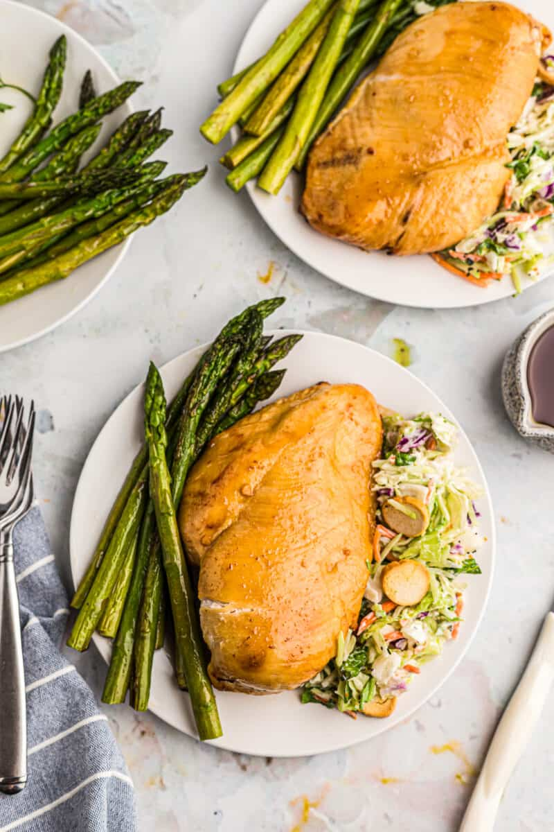 air fryer chicken breast on plate with salad and asparagus