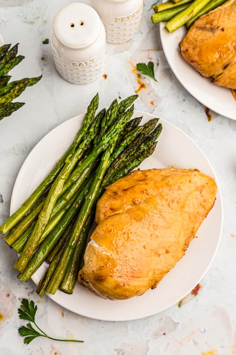 air fryer chicken breast with asparagus on white plate