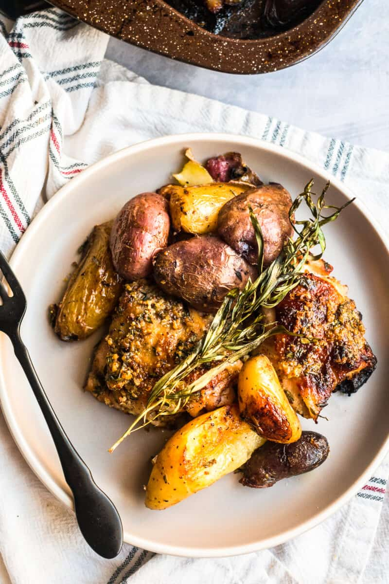 baked honey mustard chicken thighs with potatoes on plates