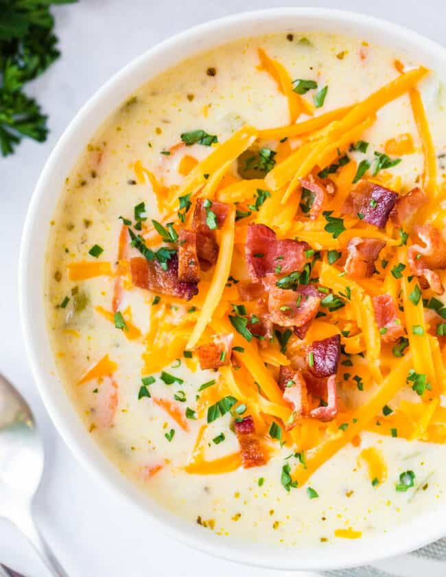 up close image of cheesy chicken chowder garnished with cheese and bacon