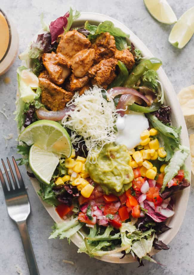 chipotle mexican chicken salad with toppings in bowl