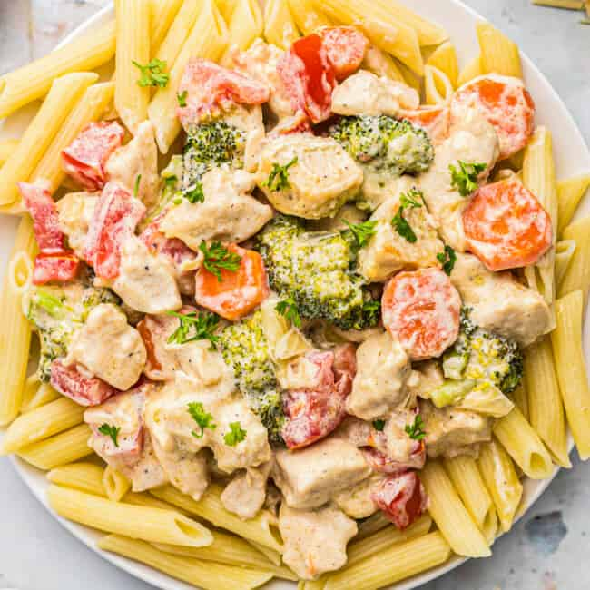 up close image of creamy chicken primavera over pasta