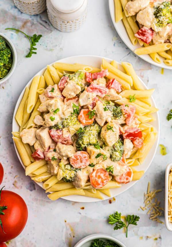 chicken primavera over pasta on plate