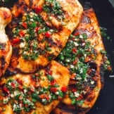 grilled chimichurri chicken on black plate