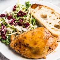 plate of maple bourbon chicken with salad and bread